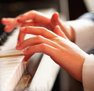 Student and Teacher Hands at Piano